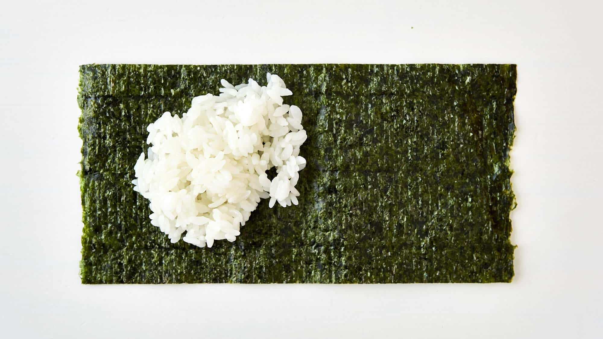 Add some rice to the rough side of the nori for Temaki Sushi.