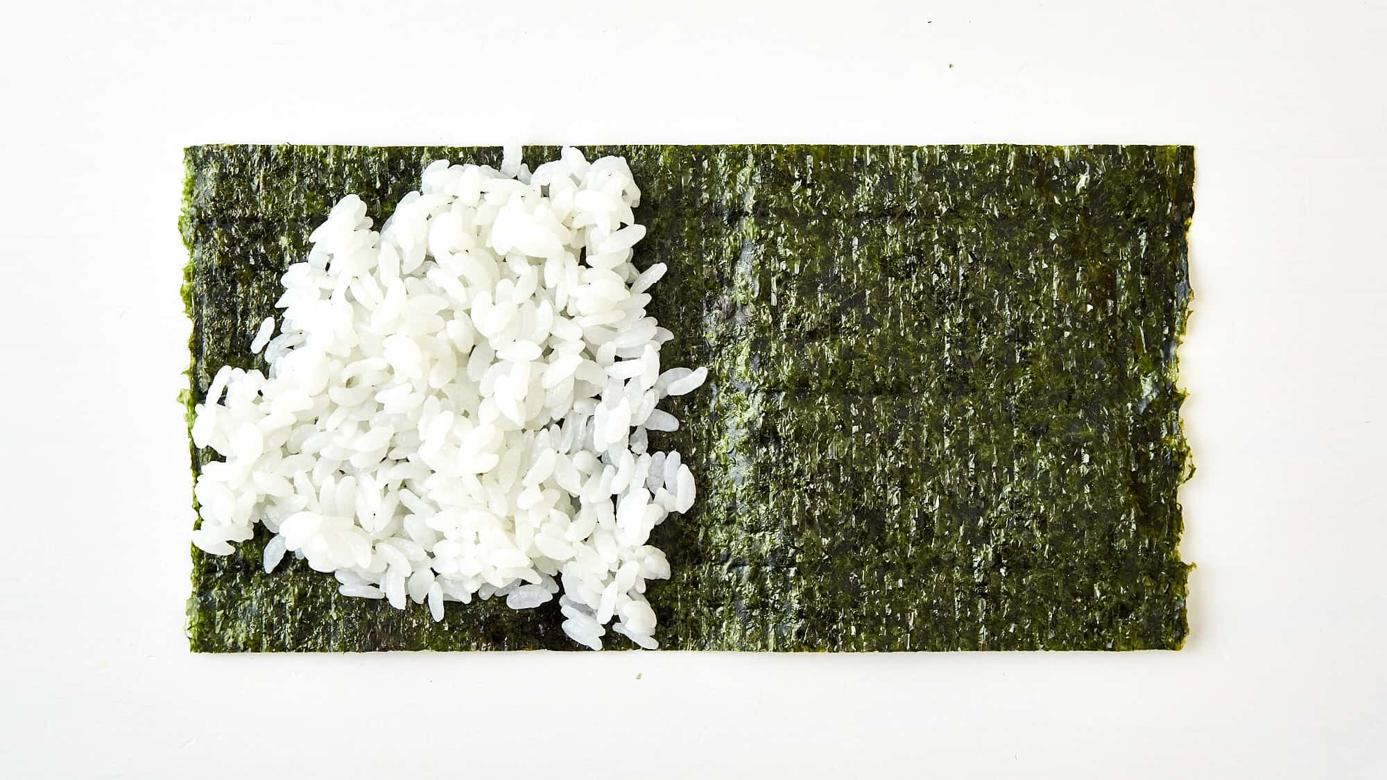 Spread the rice out into a triangle over half the nori.