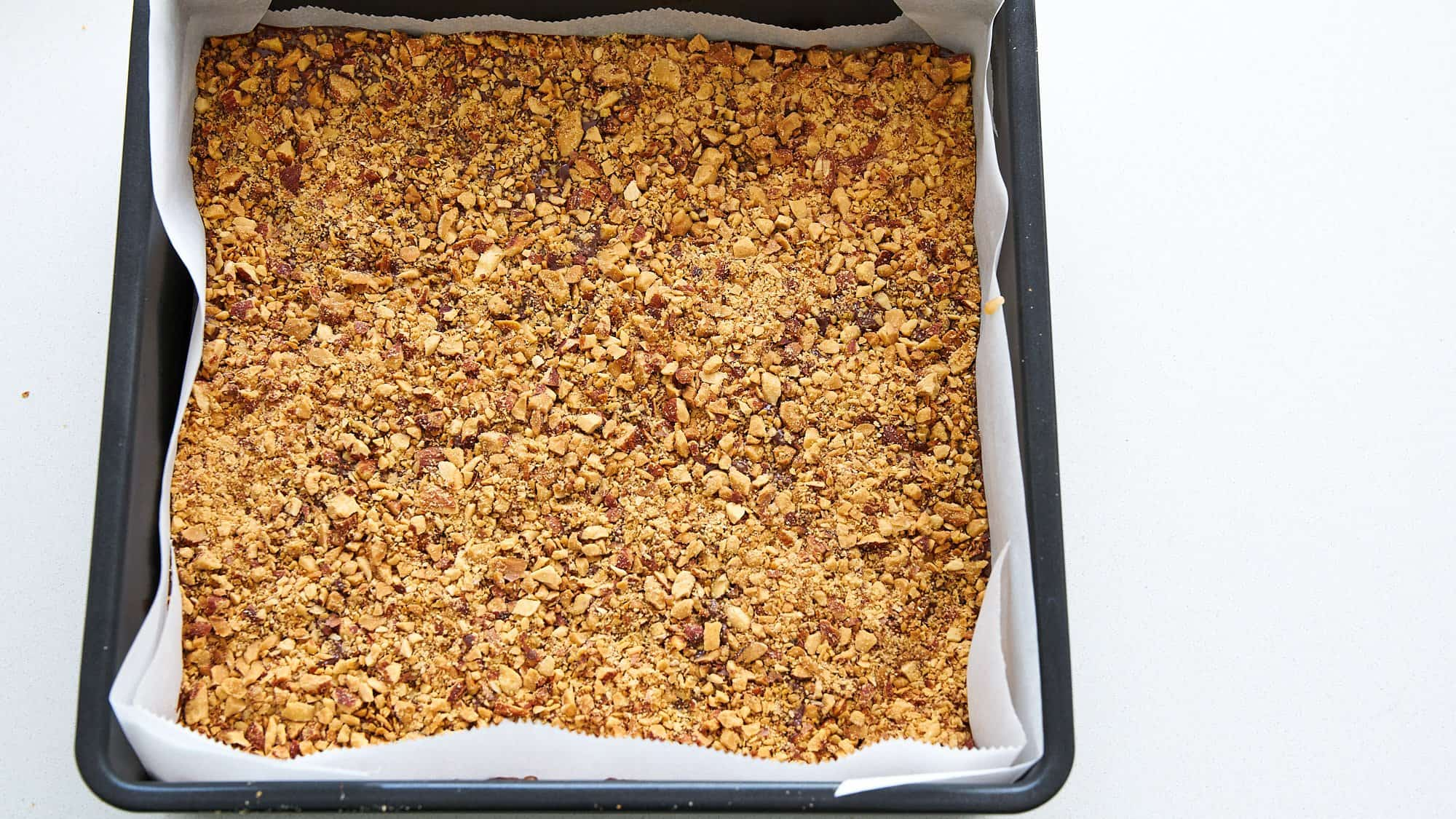 Top your butter toffee with the rest of the roasted almonds.
