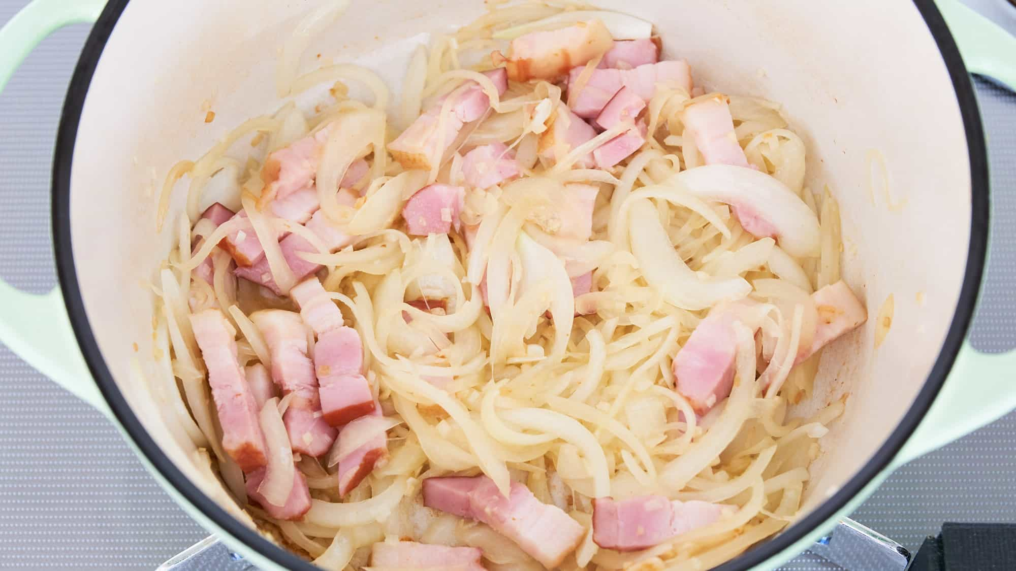 Onions, bacon and garlic, caramelized in a green dutch oven for making chicken stew.