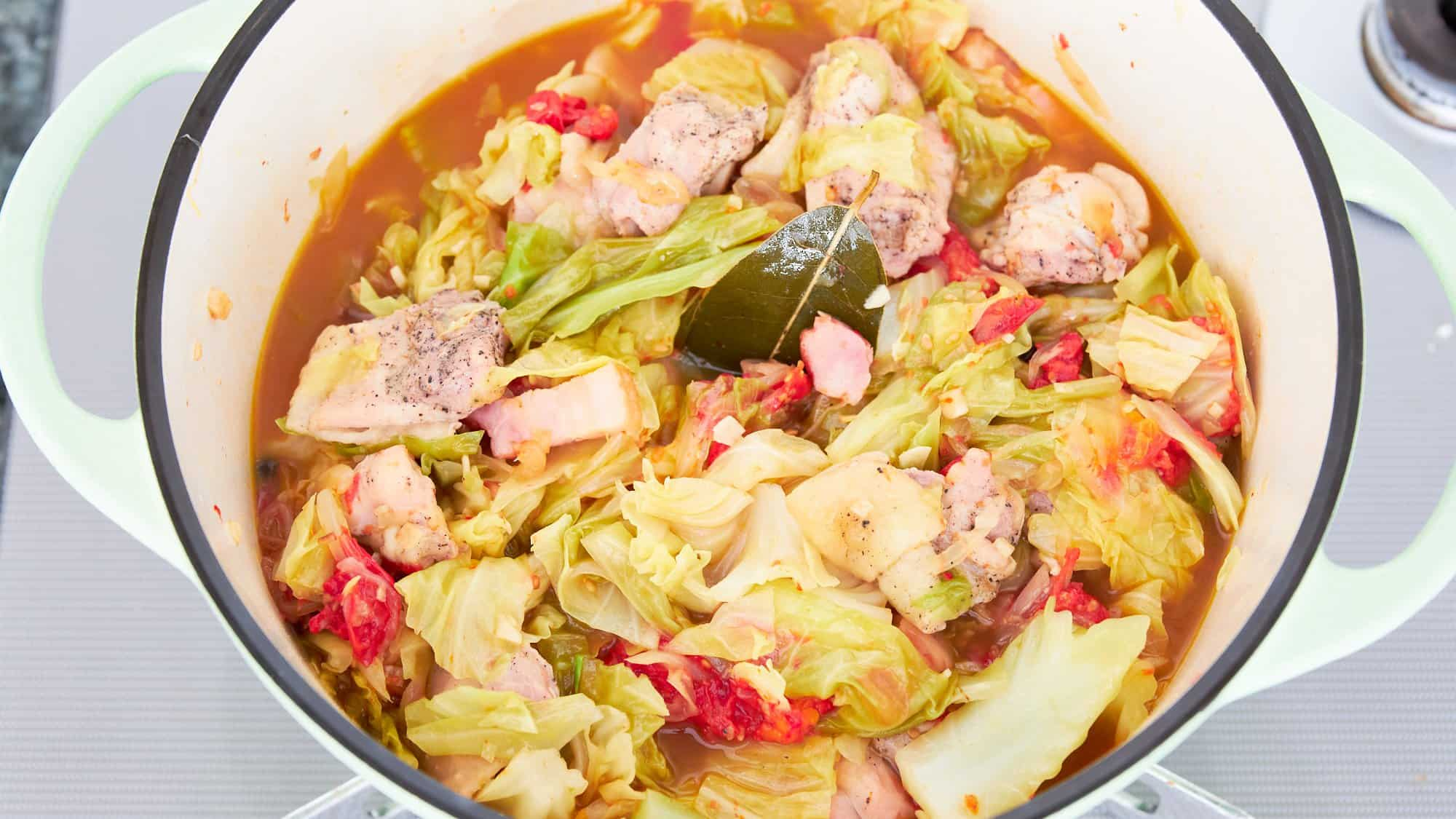 Cabbage and chicken stew in a green dutch oven on a grey stove.