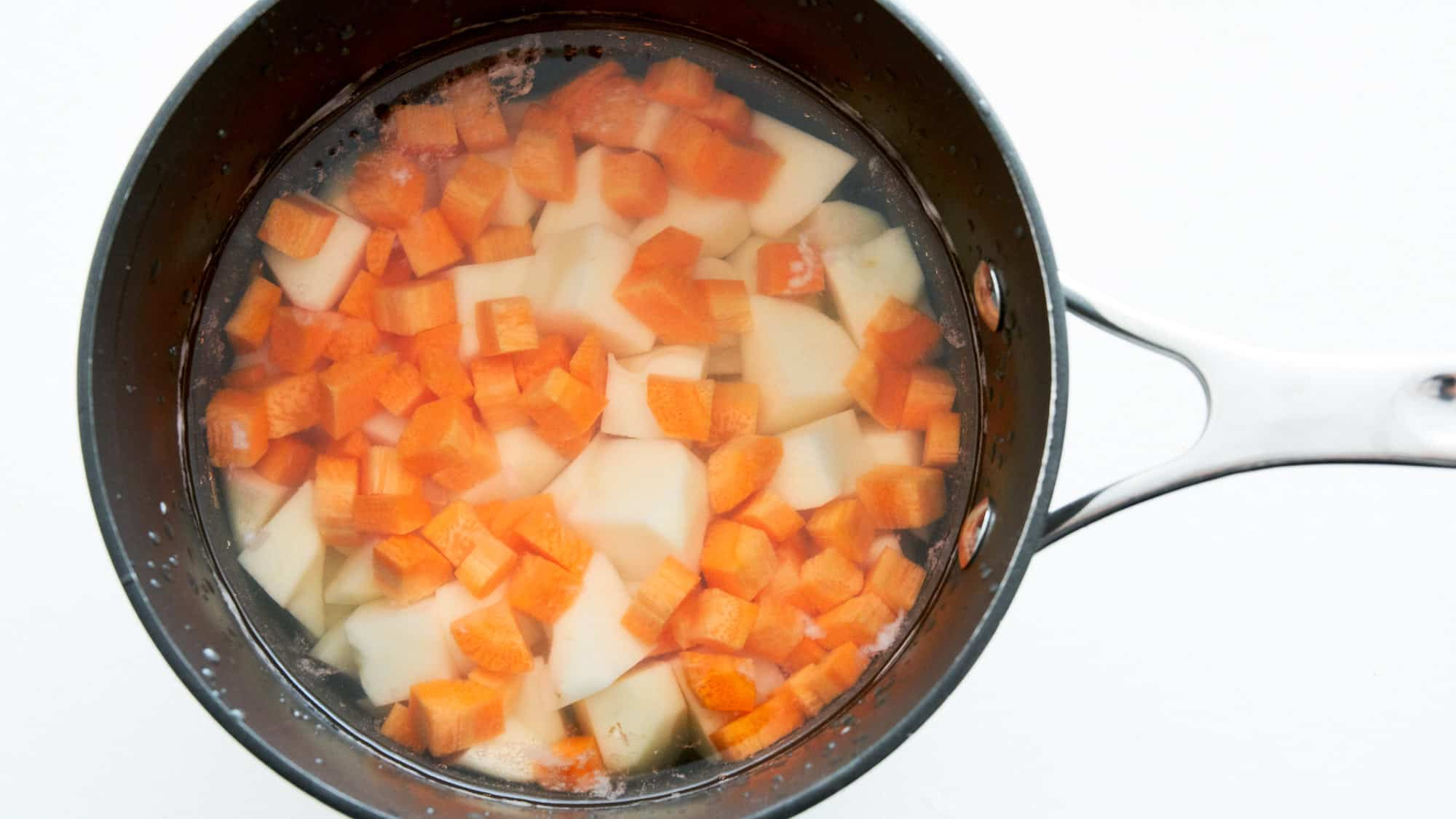 Raw potatoes and carrots cut into cubes in a pot of water. For making potato salad.