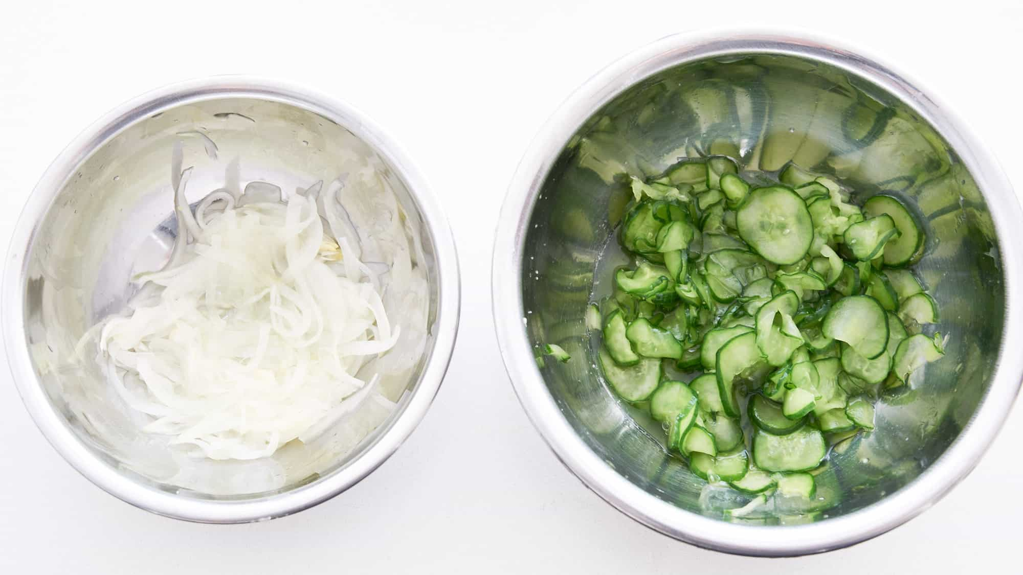 Salted onions and cucumbers in stainless steel bowls on a white counter for making Japanese style potato salad.