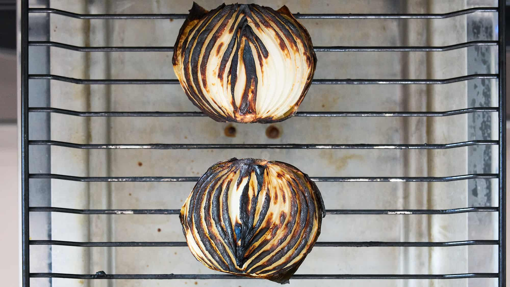 Char-grilled onion halves on grill rack for making Pot au Feu recipe.