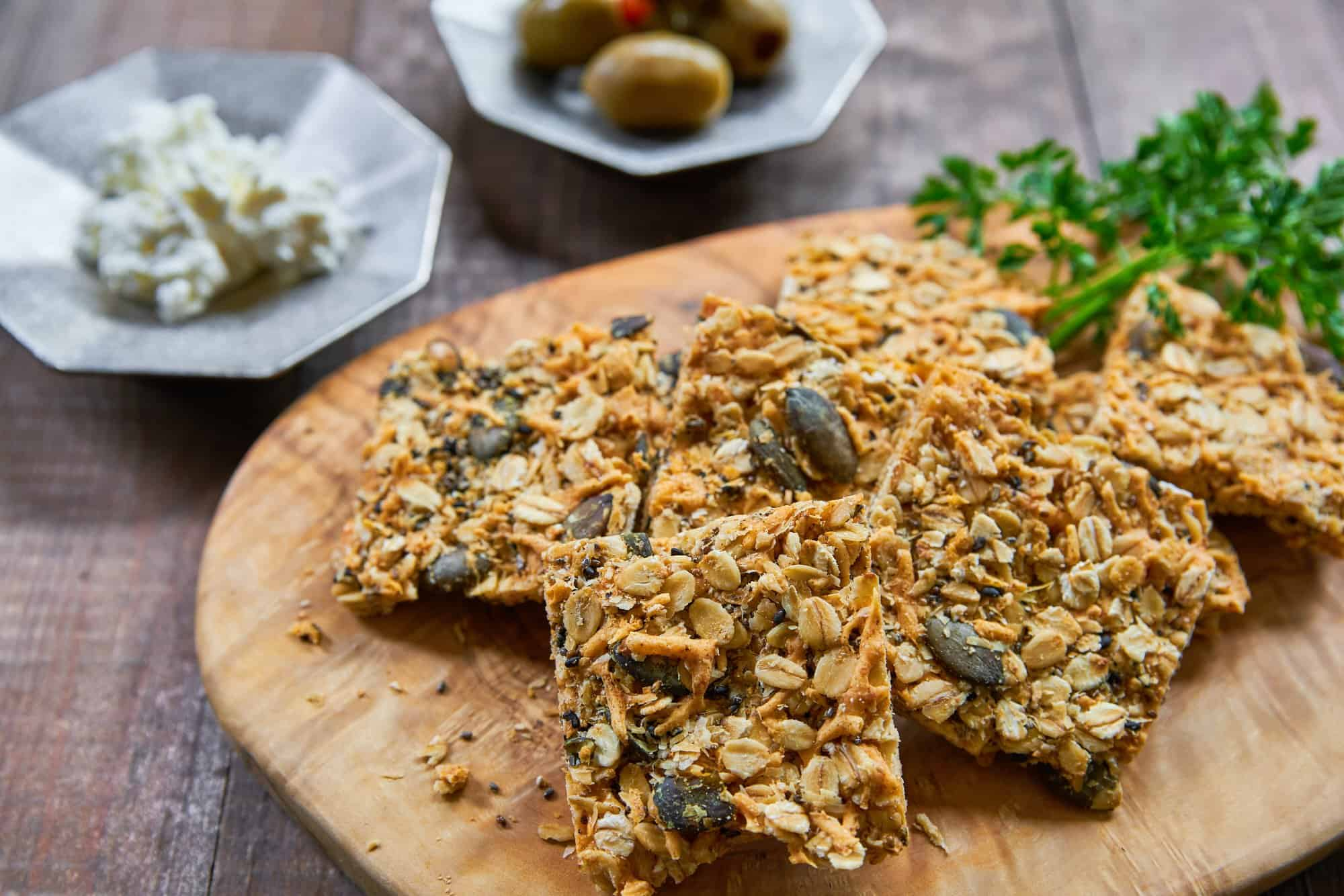 Cheesy and delicious savory granola bars are loaded with cheddar, parmesan, oats, pumpkin seeds, sesame seeds, and chia seeds and baked until crisp.