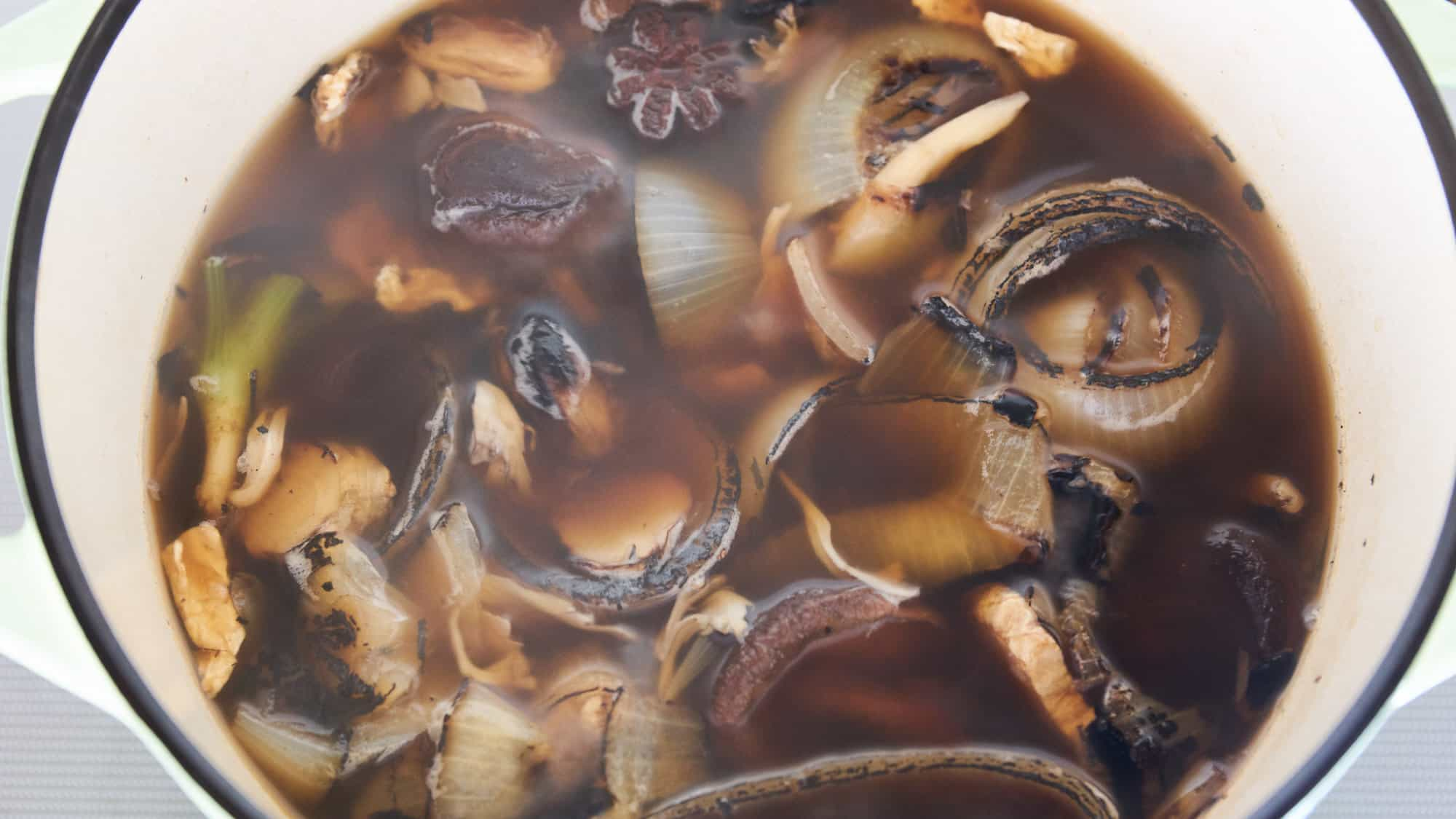Charred aromatics and dried mushrooms simmering in a dutch oven for vegan pho recipe.