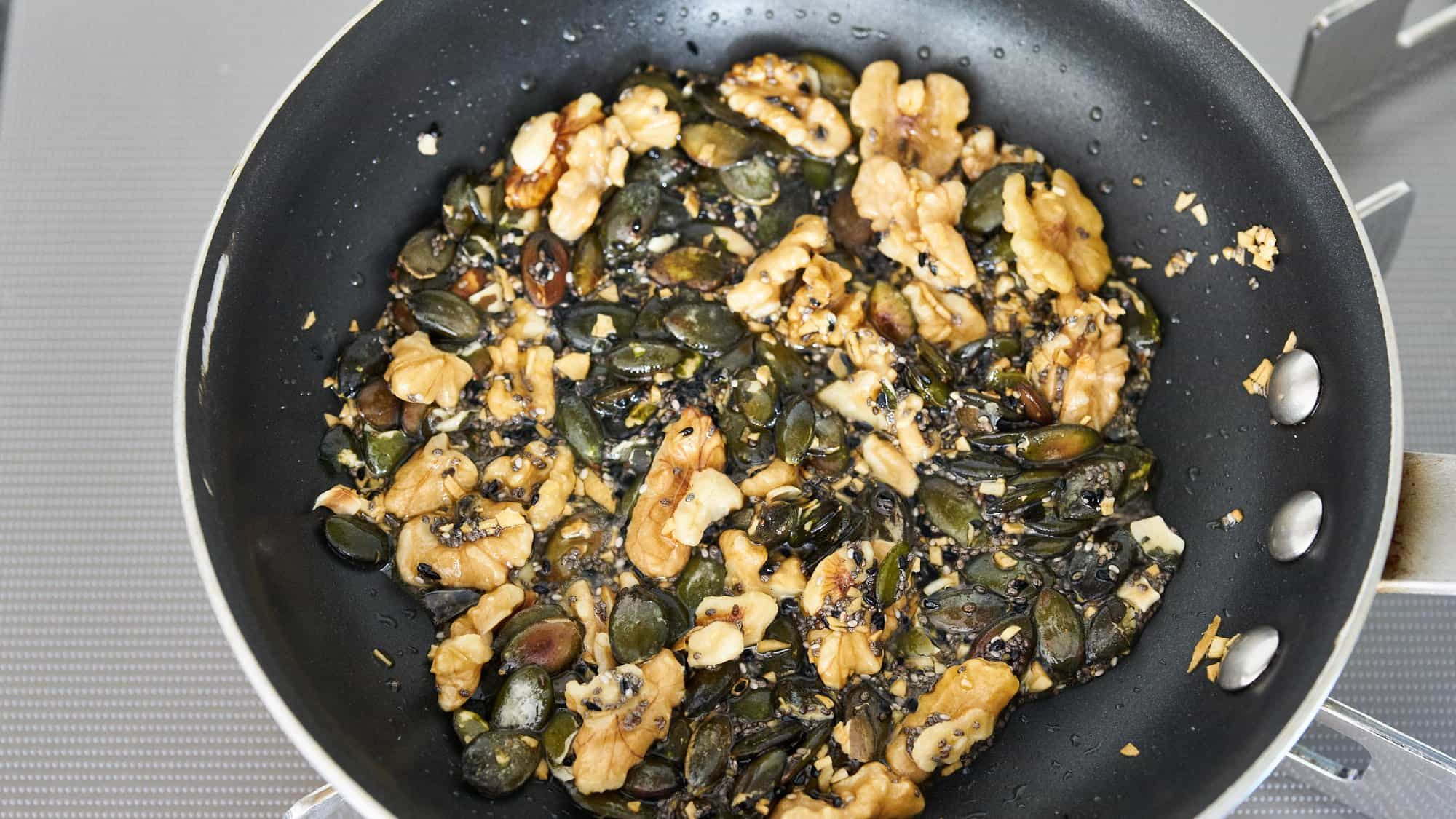 Caramelized garlic, olive oil, walnuts, pumpkin seeds, chia seeds and nigella seeds in a frying pan.