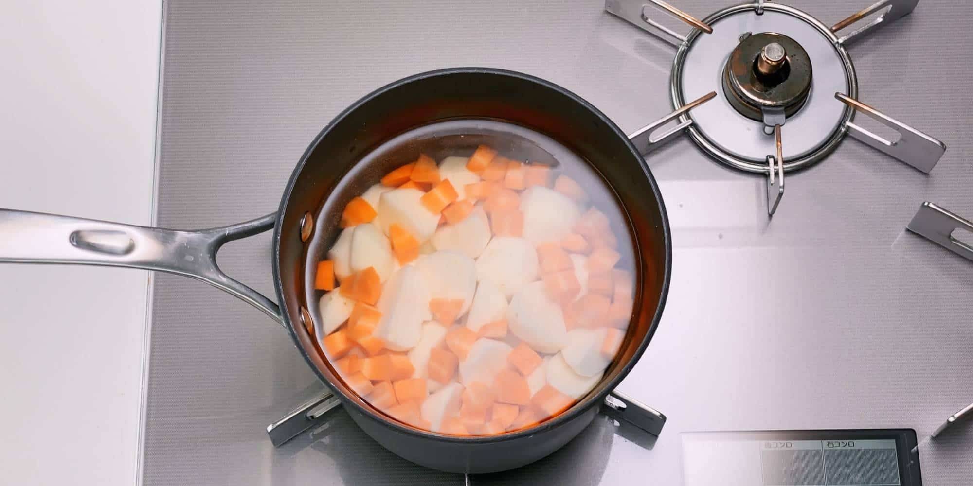 Boiling potatoes and carrots for salad.