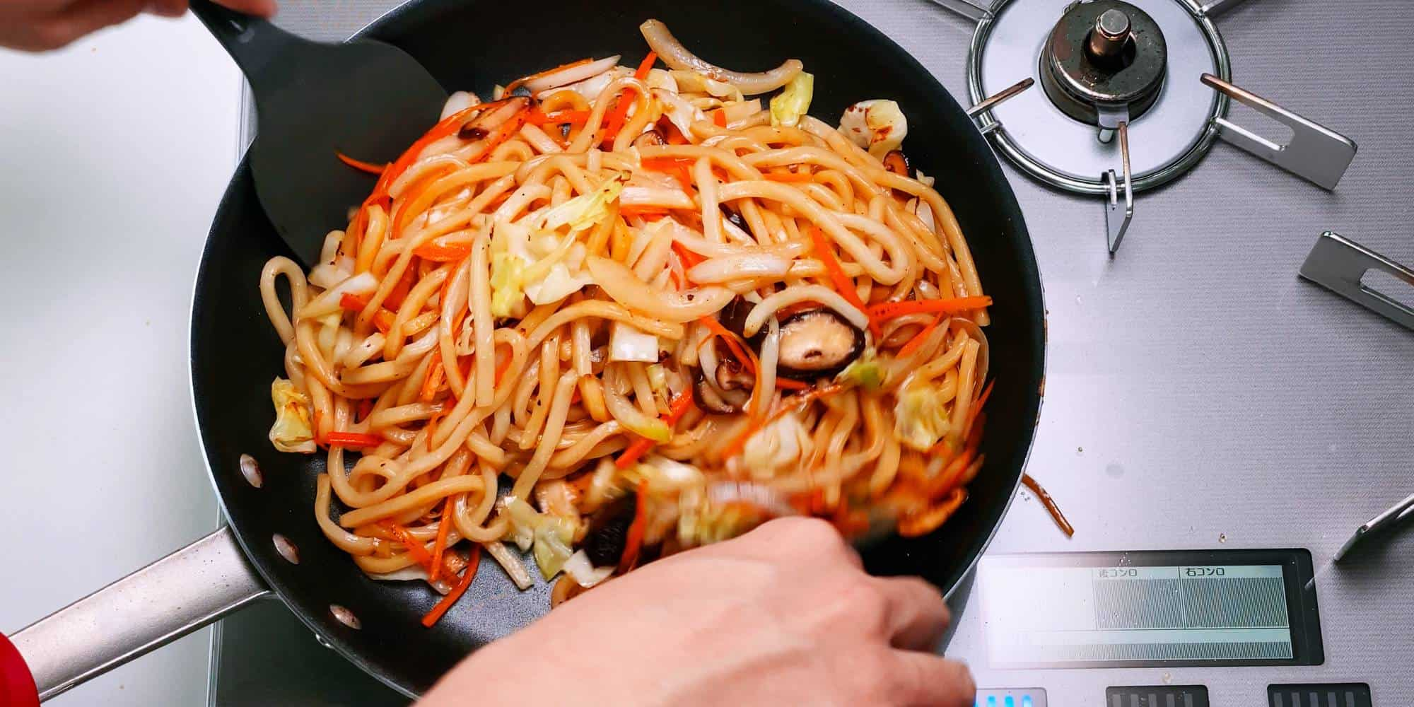 Tossing yaki udon with sauce.