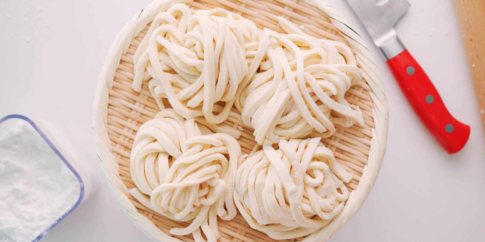 Nests of fresh hand-cut udon noodles in a basket.
