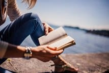 A woman reading a book by the water. Books can take you away from home when you can't get away.