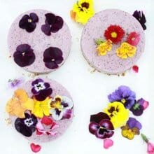 A raw berry cheesecake topped with edible flowers.