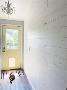 Room with yellow door and a cat laying in front of it
