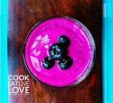 PInk smoothie topped with blueberries