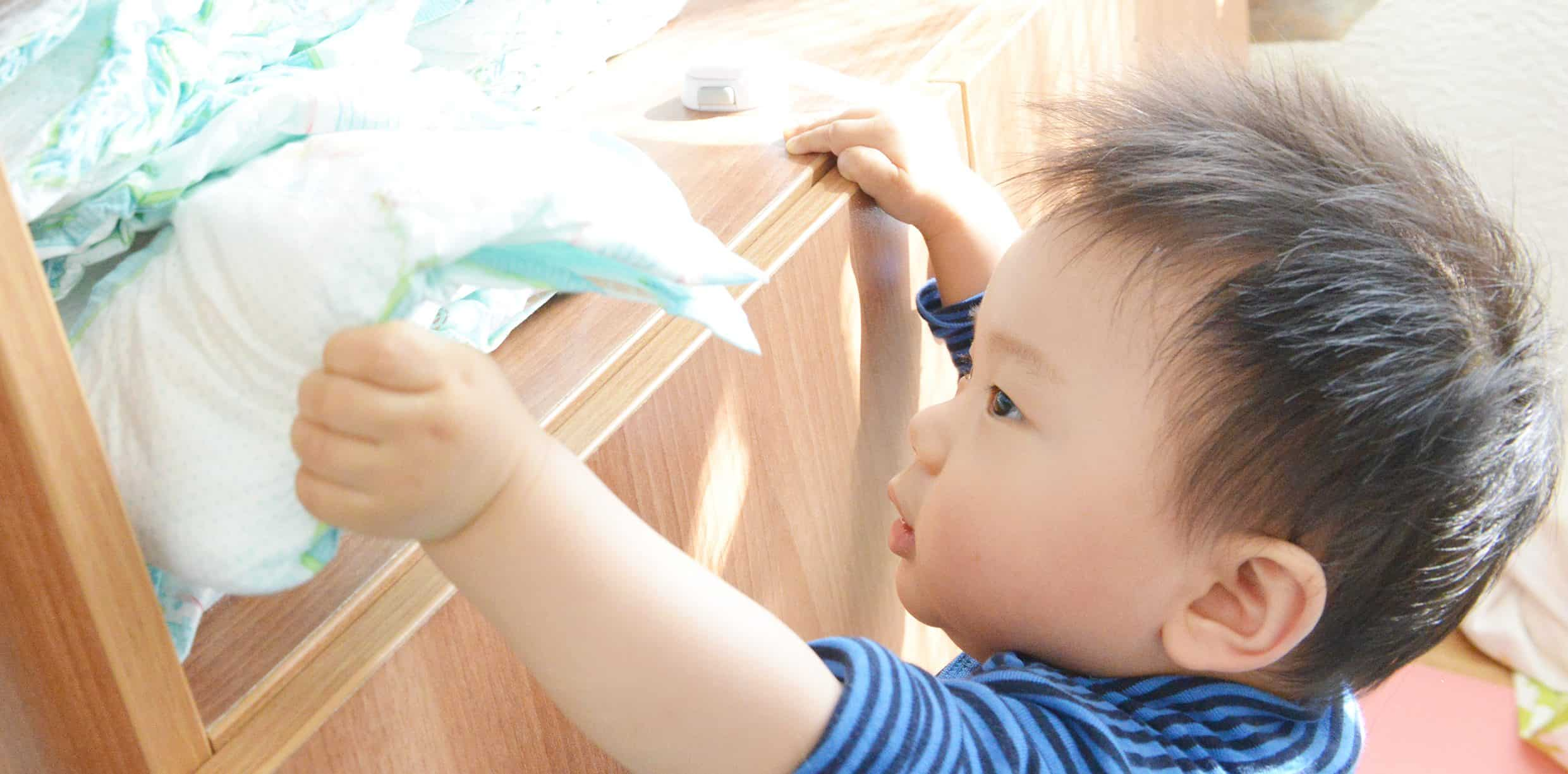 child reaching for nappies- potty training