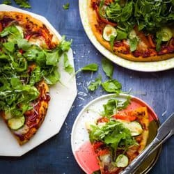Overhead shot of vegetable pizza on a chopping board beside a plate with a slice of pizza