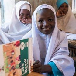 Nigerian girl reading in classroom.