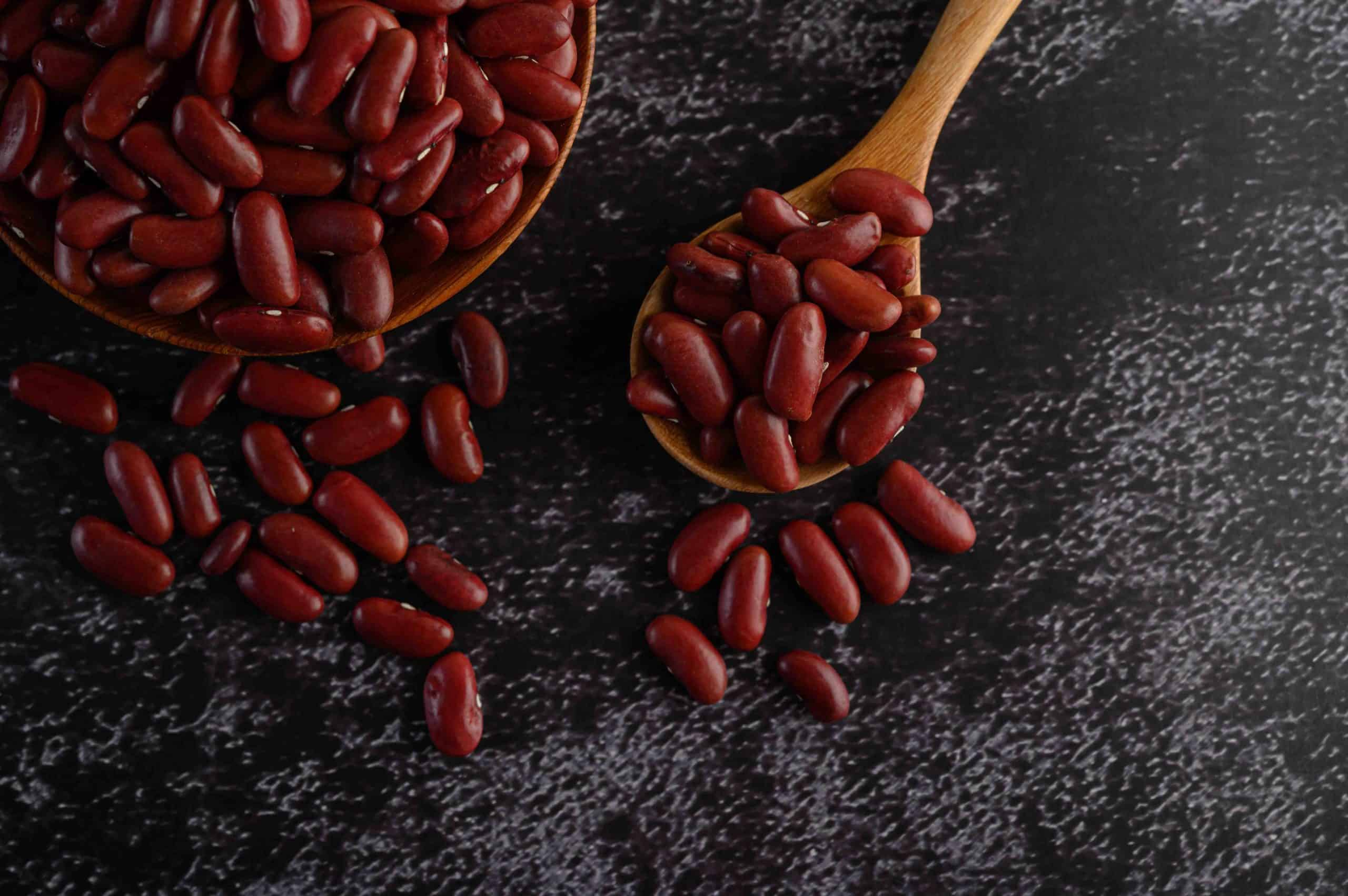 Red beans in a wooden bowl and wooden spoon on the black cement floor
