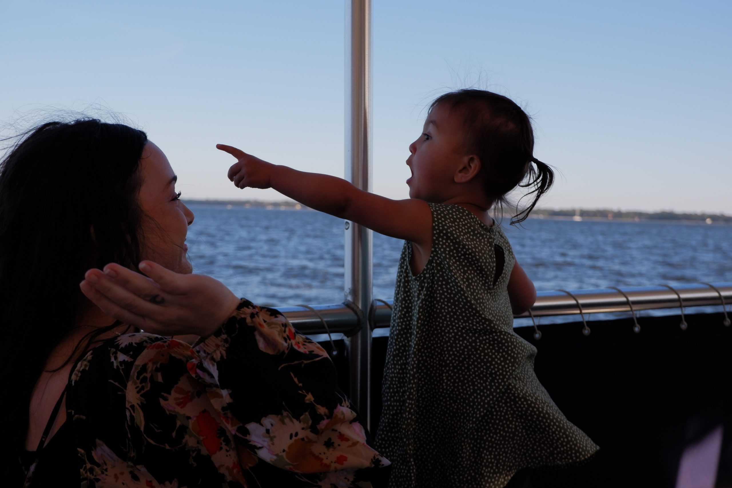 Young kid excitedly pointing to something in the distance from the boat. Family boat charters Charleston, SC