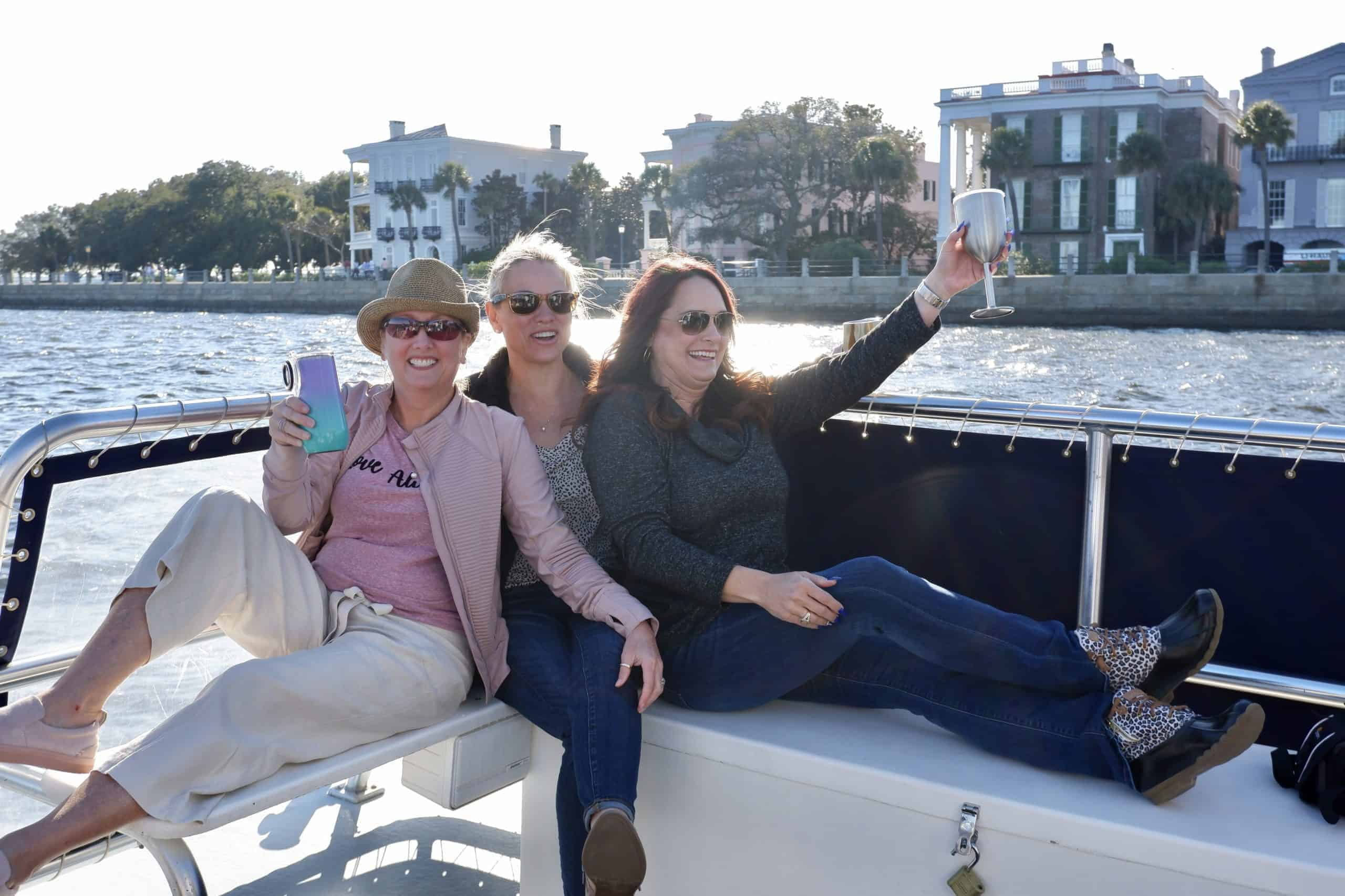 Women raising their glasses on the boat with sun shining down on The Battery. Private charter Charleston, SC