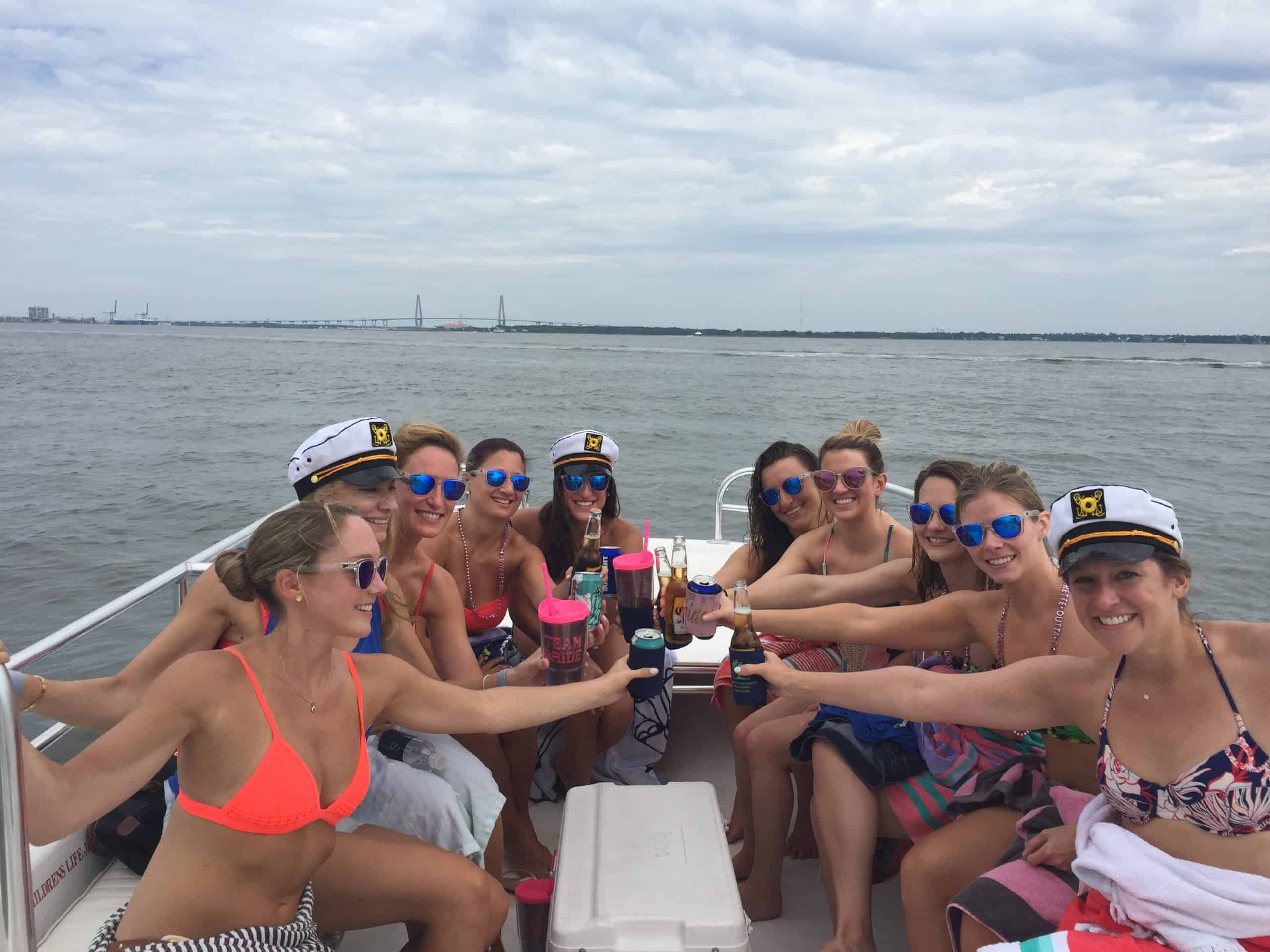 Group of women using their drinks to cheers together on the boat. Private booze cruise
