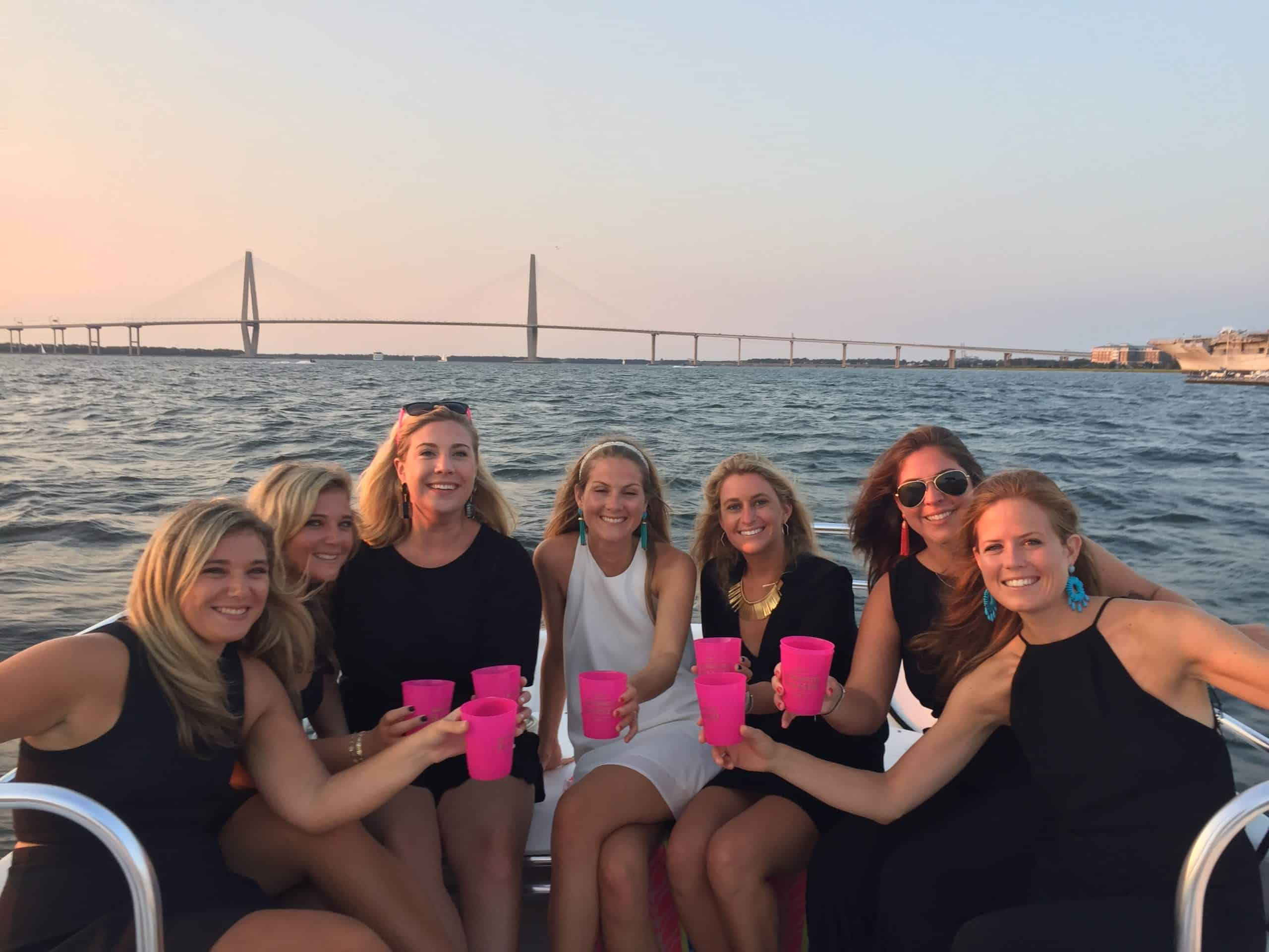 Group of women dressed up on the boat, toasting with their drinks. Private booze cruise