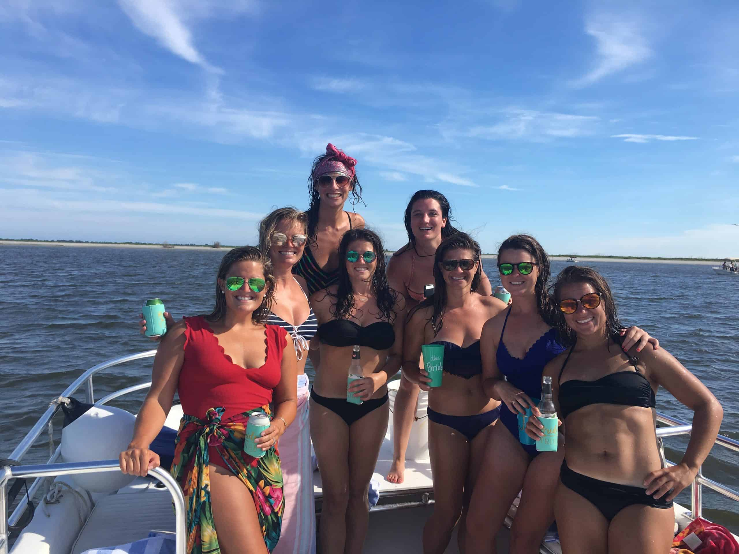 Group of women gathered on the boat for a drink after swimming in the water. Charleston booze cruise bachelorette
