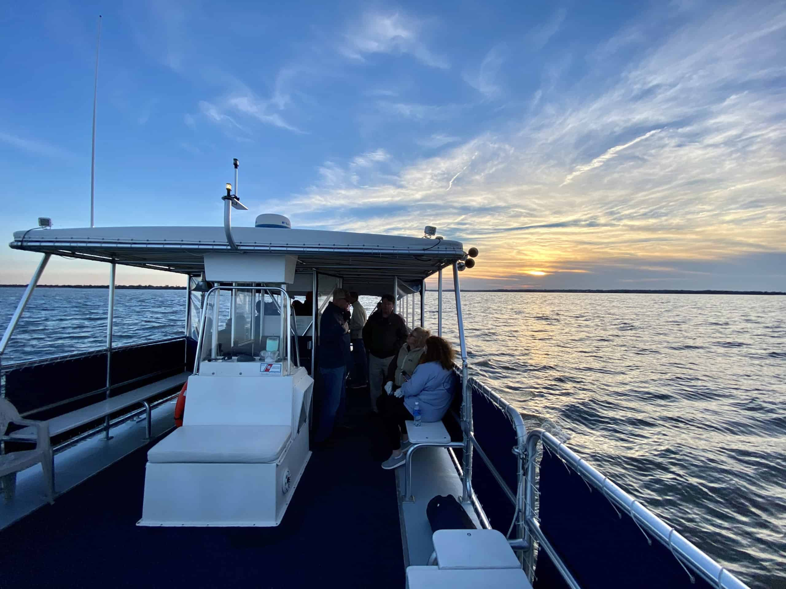 Sun setting on the water behind the boat. Private charter Charleston, SC