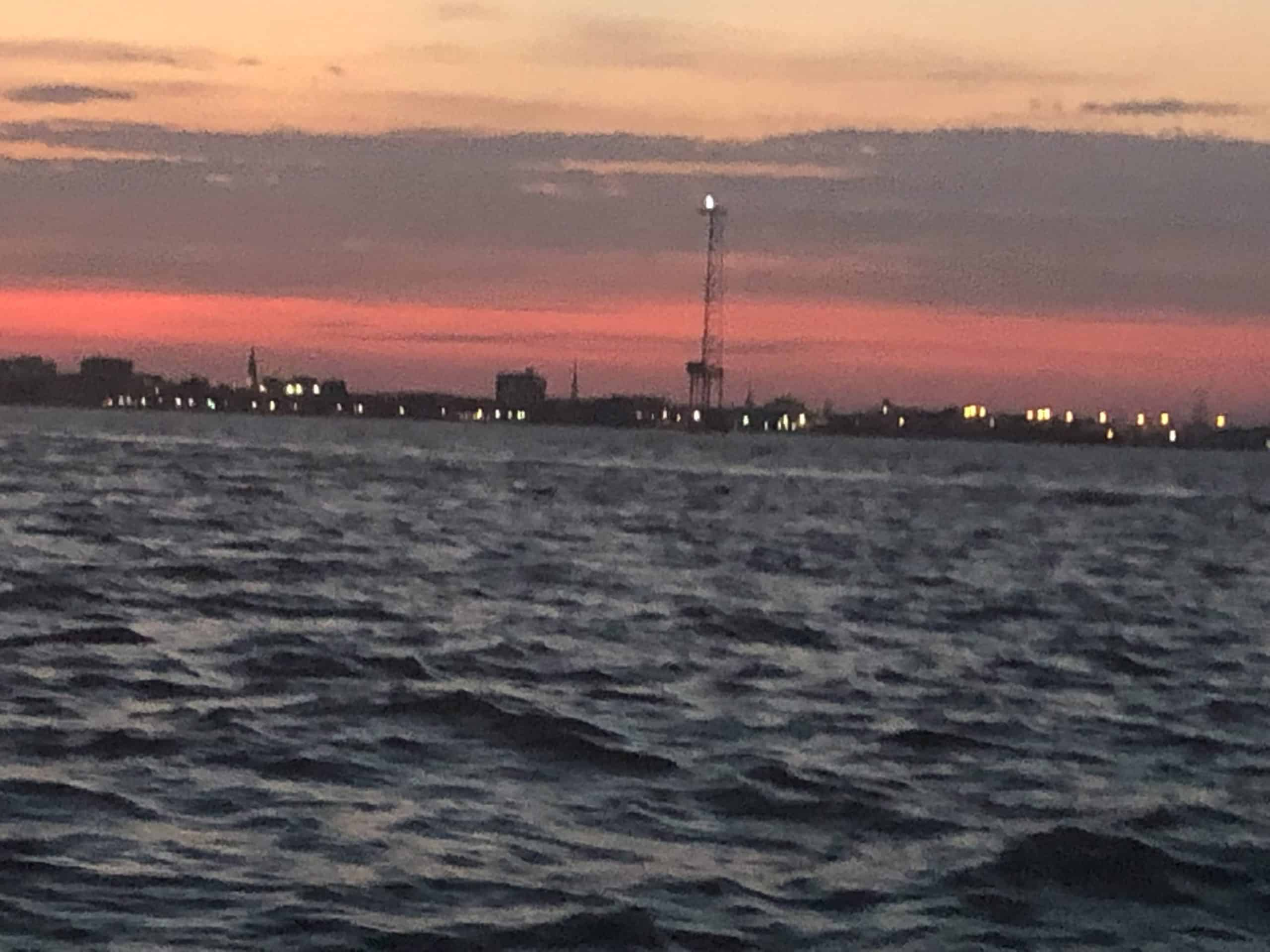 Pink sunset over city horizon. Sunset cocktail cruise Charleston, SC