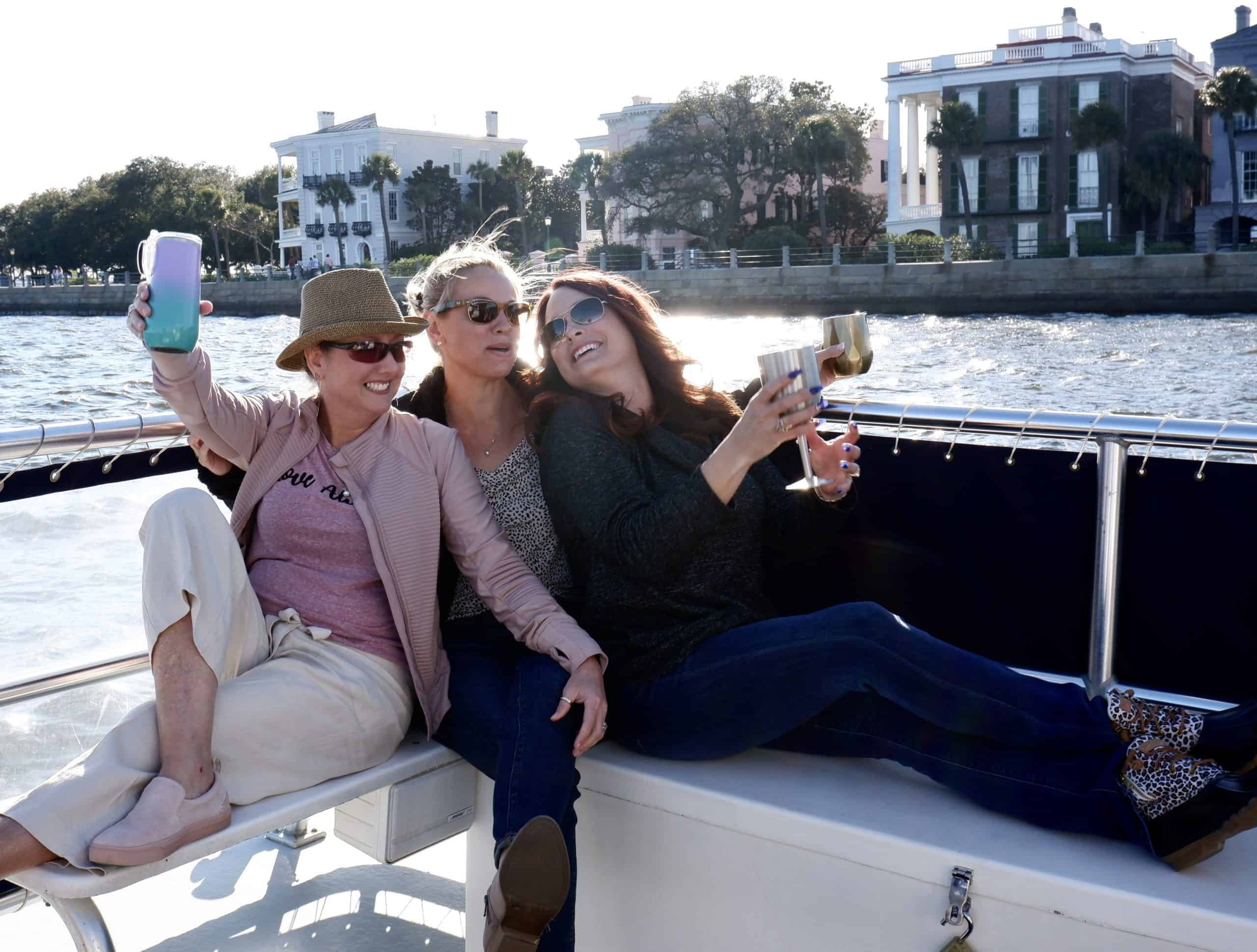 Women raising their glasses together on the boat with sun shining down on The Battery. Private charter Charleston, SC