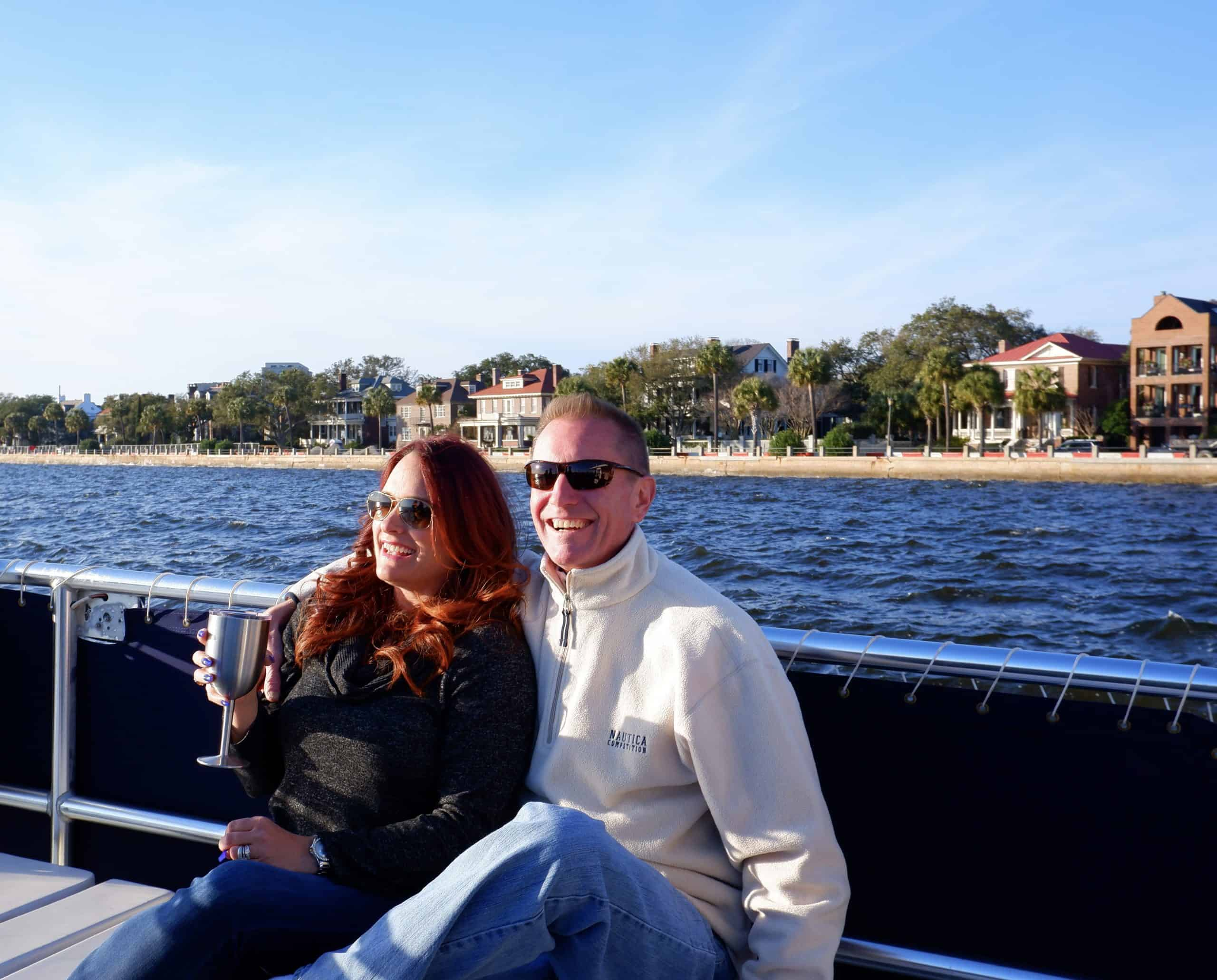 Couple pictured on the boat with The Battery in the background. Party boat rental Charleston, SC