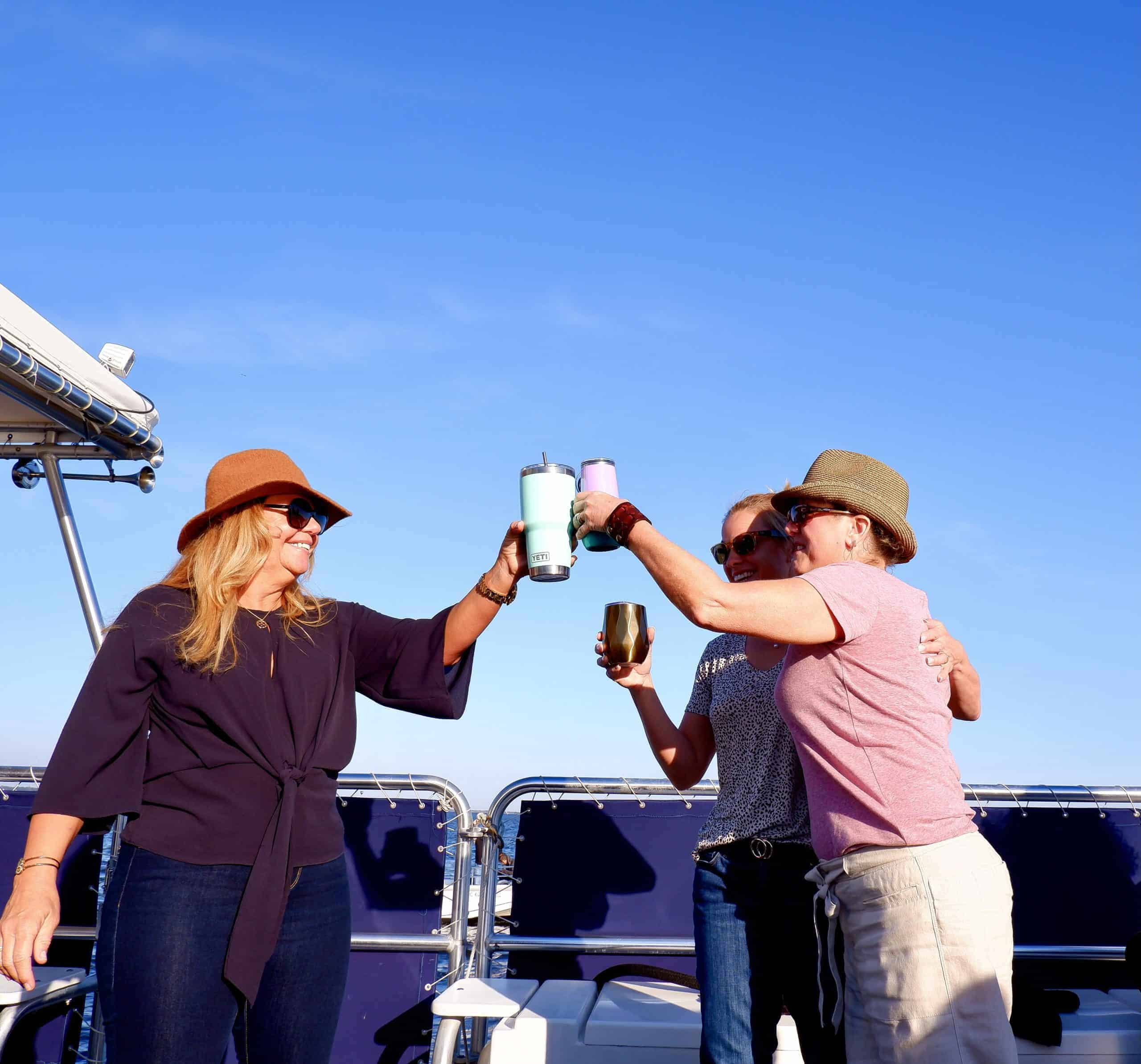 Three women raising their glasses to cheers together. Party boat rental Charleston, SC