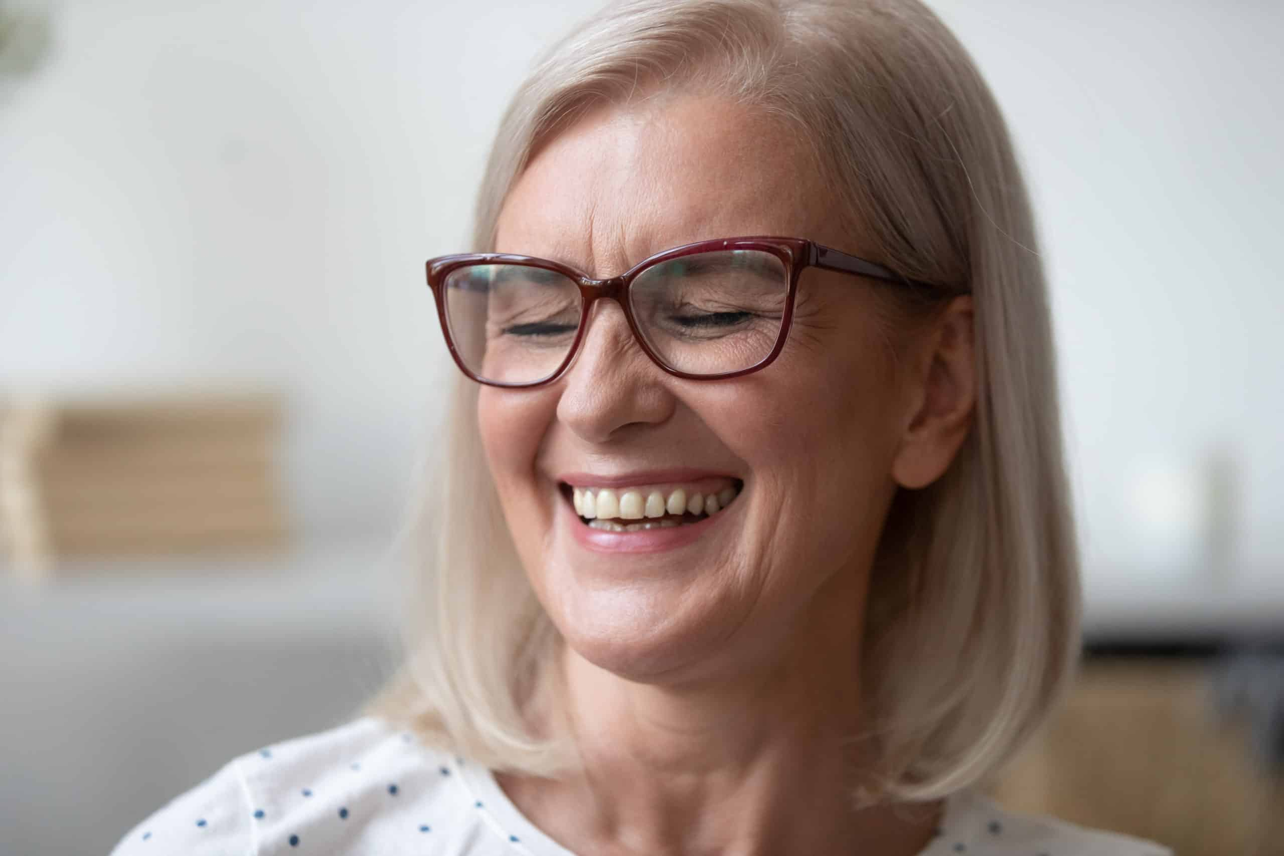 Close up of overjoyed lady in glasses smile showing white healthy teeth