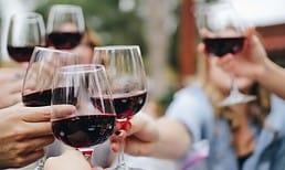 Glasses of red wine being held in cheers