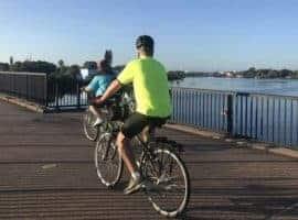 Bicyclists on bridge over water.