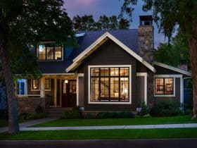 a welcoming exterior with dark grey paint, white trim, and dark wood door