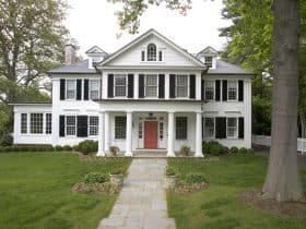 a white house with black shutters and coral red front door