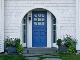 a unique entry design with navy Dutch-style front door