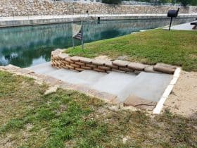 the combination of steps and concrete bags retaining walls in a riverside