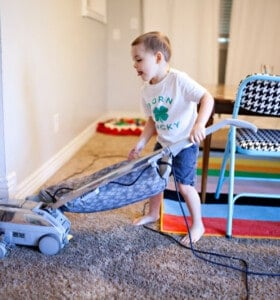 Kid cleaning house by using a vacuum on an area rug