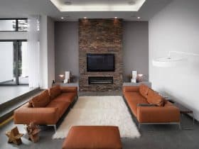 grey and brown living room with a brick wall