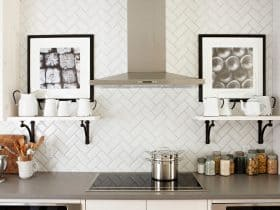 Herringbone style beveled white subway tile with gray grout detail