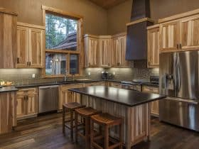 cozy contemporary kitchen with non-stained hickory cabinets and multicolor dark wood floor
