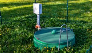 A green septic tank with control panel beside it for the effluent pump