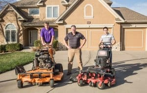 three lawn care workers with their mowers in the driveway