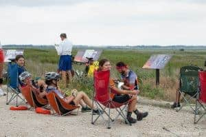 Cross-country cyclists taking a break at a turnoff with a view of Quivera National Wildlife Refuge