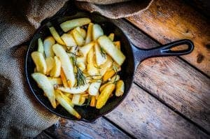 Homemade french fries with rosemary and salt in cast iron skille