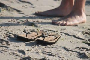 Sandalen und nackte Füße am Strand