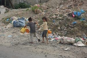 Two children holding plastic jugs walk away from the camera past a pile of rubble. One of the children is looking over her shoulder smiling.
