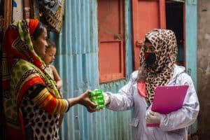 Tanzima Akter, works as a community facilitator under the LIUPC project of UNDP Bangladesh. Here she is distributing anti-bacterial and disinfecting soap to a family in Dhaka.